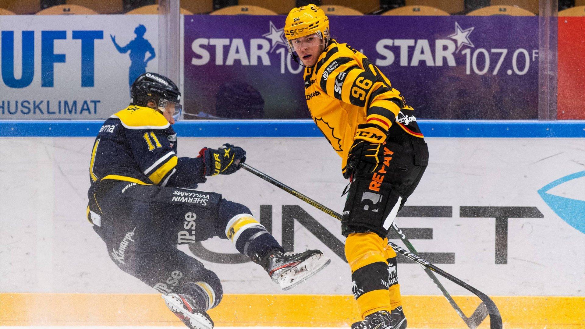 En HV71-spelare ramlar framför en Skellefteåspelare längs sargen